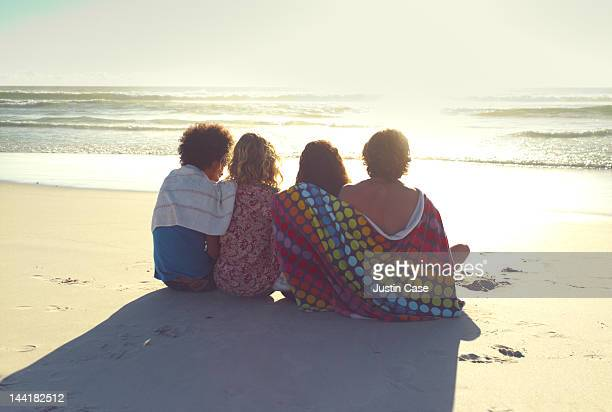Group of friends sitting on a beach while sunset