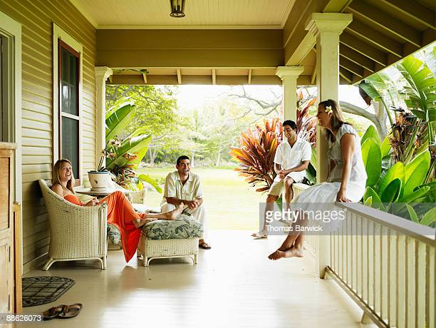 Group of friends sitting on front porch laughing