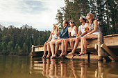 Group of happy young friends having fun and drinking beer while sitting on the jetty at the lake. Young men and woman enjoying a day on Lake.
