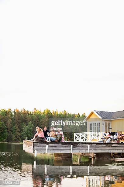 Group of friends sitting on pier at summer house