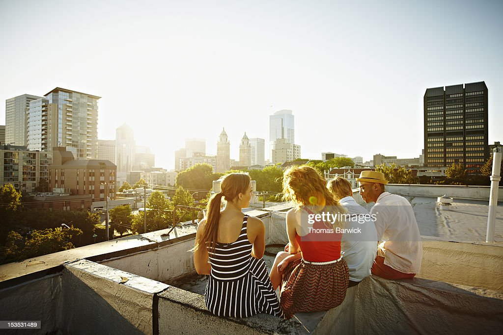 Group of friends sitting on roof at sunset : Stock Photo