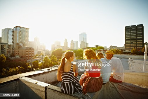 Group of friends sitting on roof at sunset