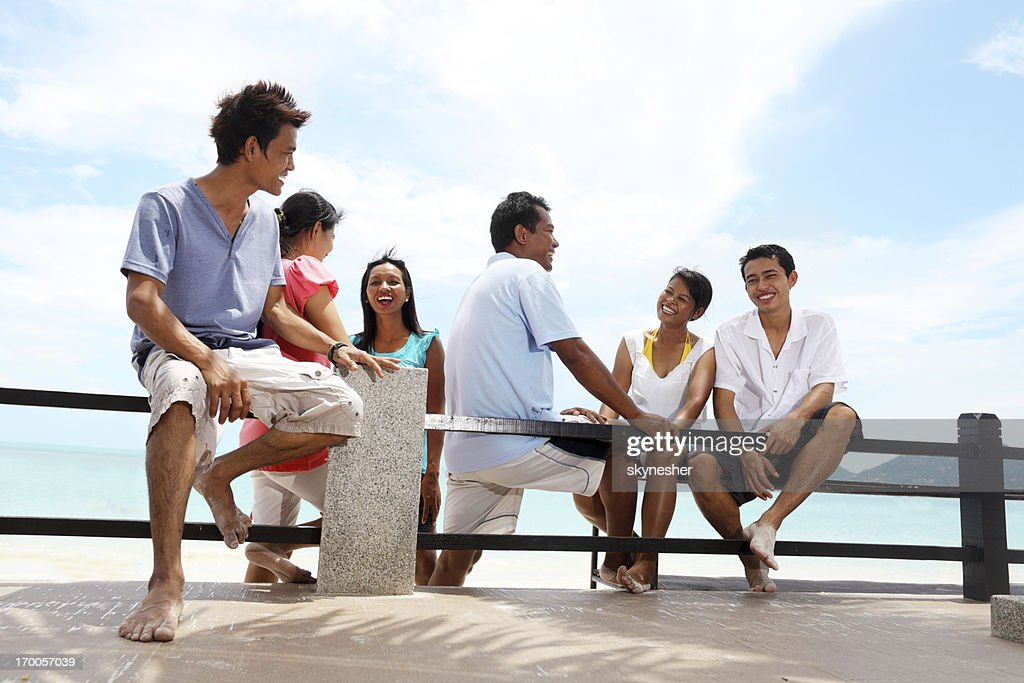 Group of friends sitting on the bench at beach.