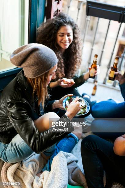 Group of friends sitting on the floor eating pizza and salad and drinking beer at home