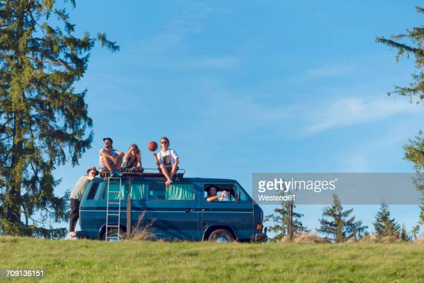 Group of friends sitting on van in the nature