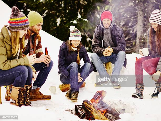 Group of friends sitting outdoors around fire