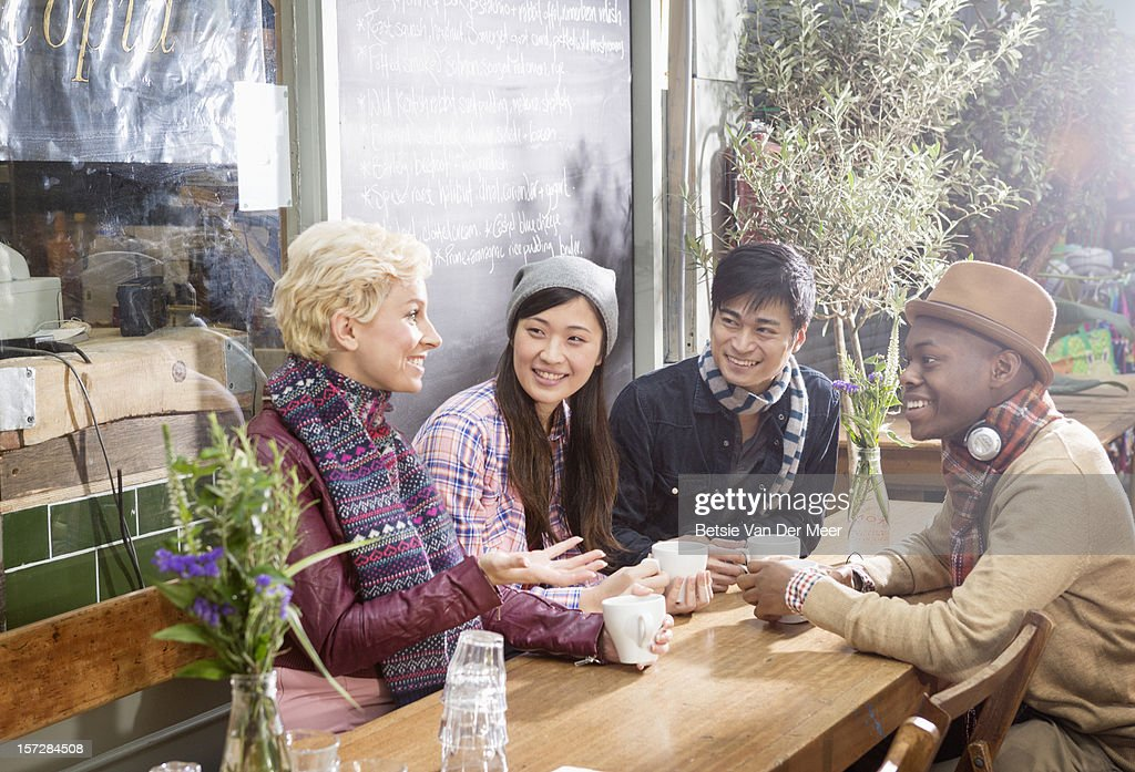 Group of friends sitting outside cafe with coffees : Stock Photo