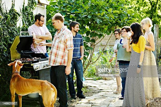 Group of friends standing around grill together