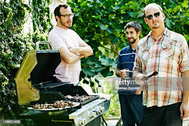 Group of friends standing around while barbecuing