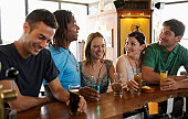 Group of friends standing at bar, smiling