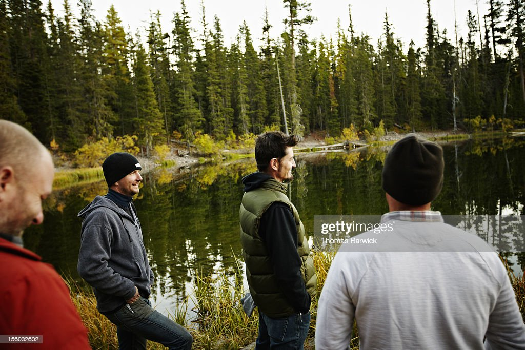 Group of friends standing by mountain lake : Stock Photo