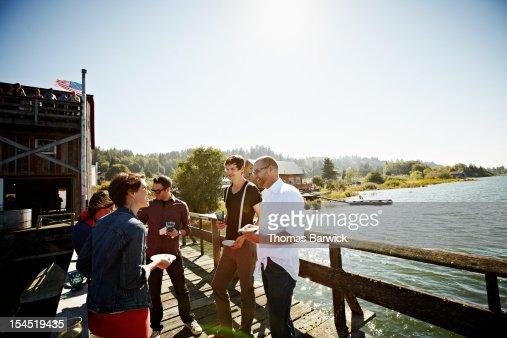 Group of friends standing eating on dock in sun : Bildbanksbilder