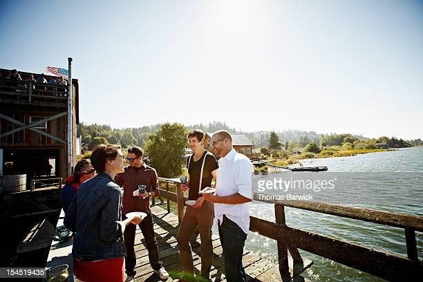 Group of friends standing eating on dock in sun