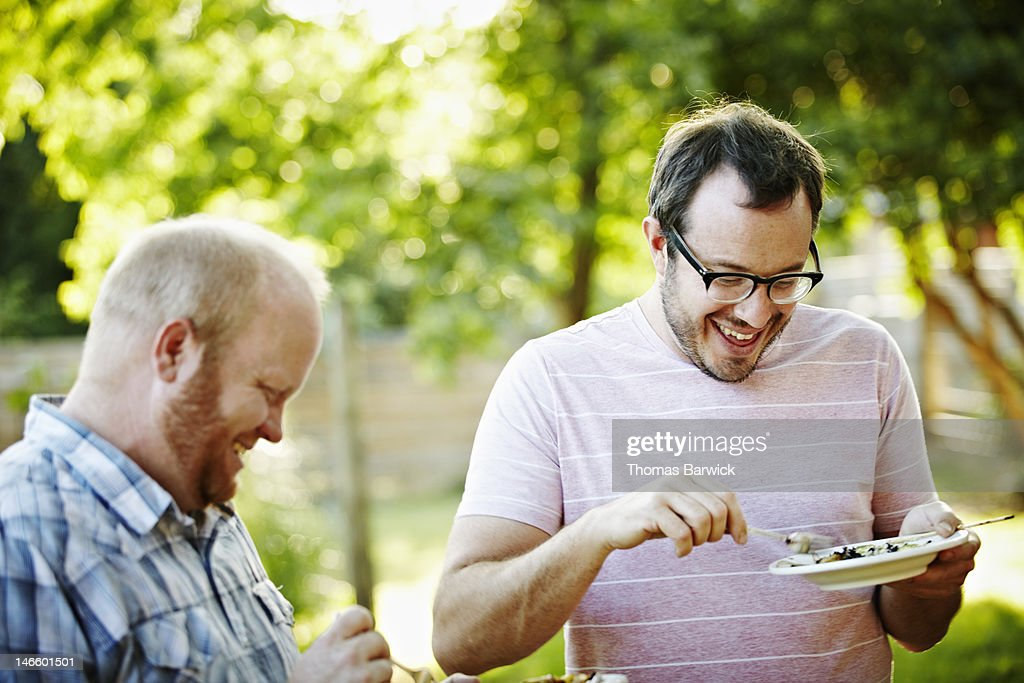 Group of friends standing in backyard eating food : Stock Photo
