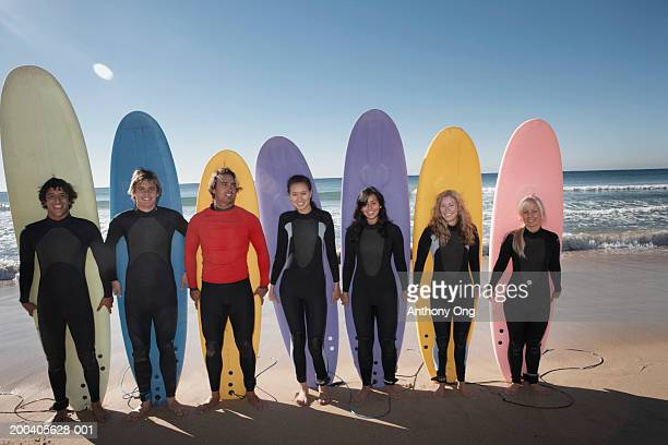 Group of friends standing on beach in front of surfboards, smiling