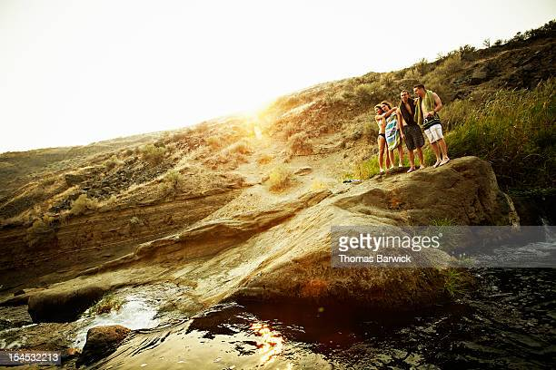 Group of friends standing on rock at sunset