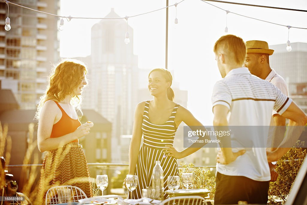 Group of friends standing on rooftop deck laughing : Stock Photo
