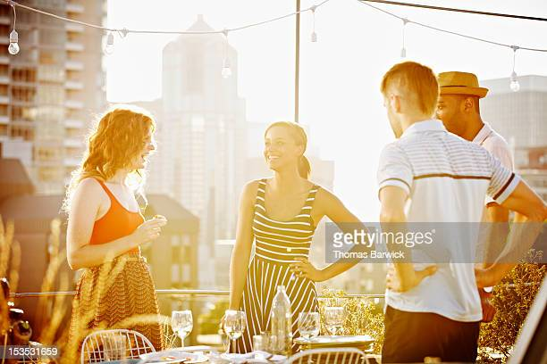 Group of friends standing on rooftop deck laughing