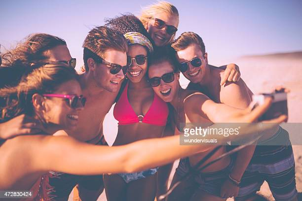 Group of friends taking a group selfie on a beach