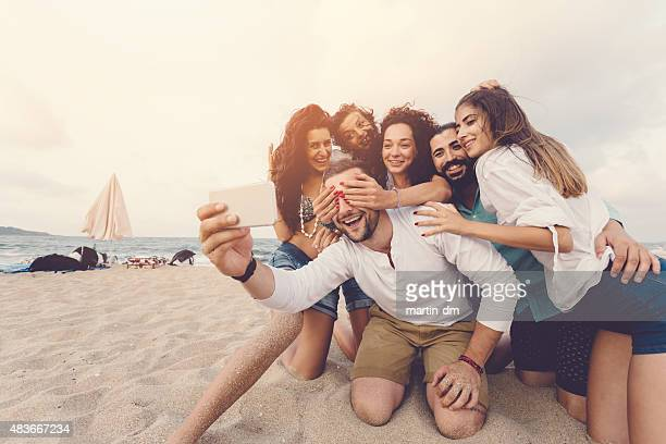 Group of friends taking a selfie at the beach