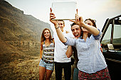 Group of friends taking photo with digital tablet