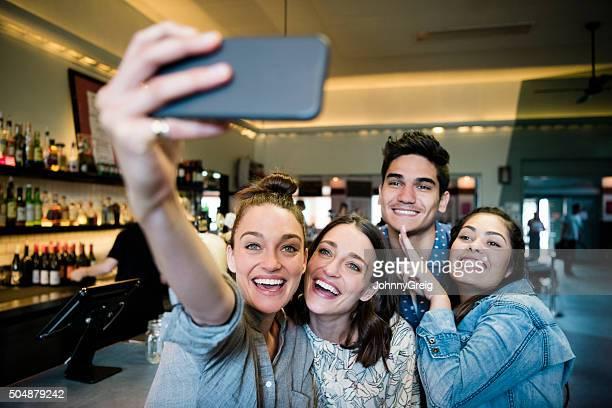 Group of friends taking selfie in bar, smiling