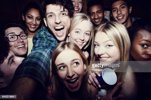 Group of friends taking selfies at a party