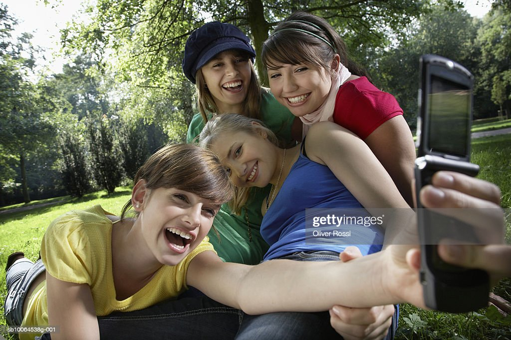 Group of friends (14-19) taking self-photo with mobile phone in park : Stock Photo
