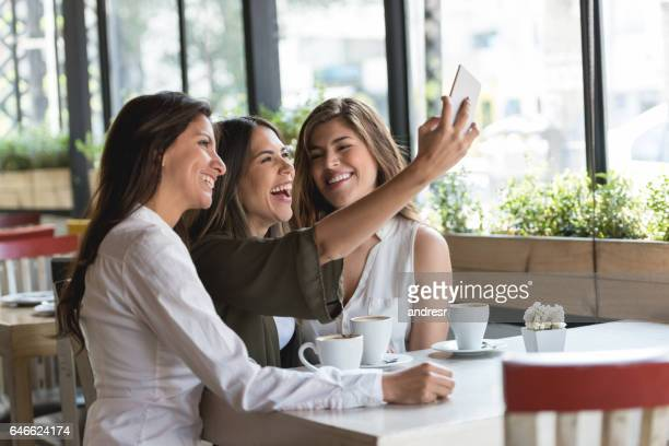 Group of friends talking a selfie at a restaurant