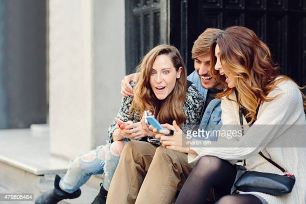 Group of friends texting on smartphones