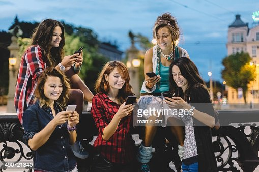 Group of friends texting on smartphones : Stock Photo