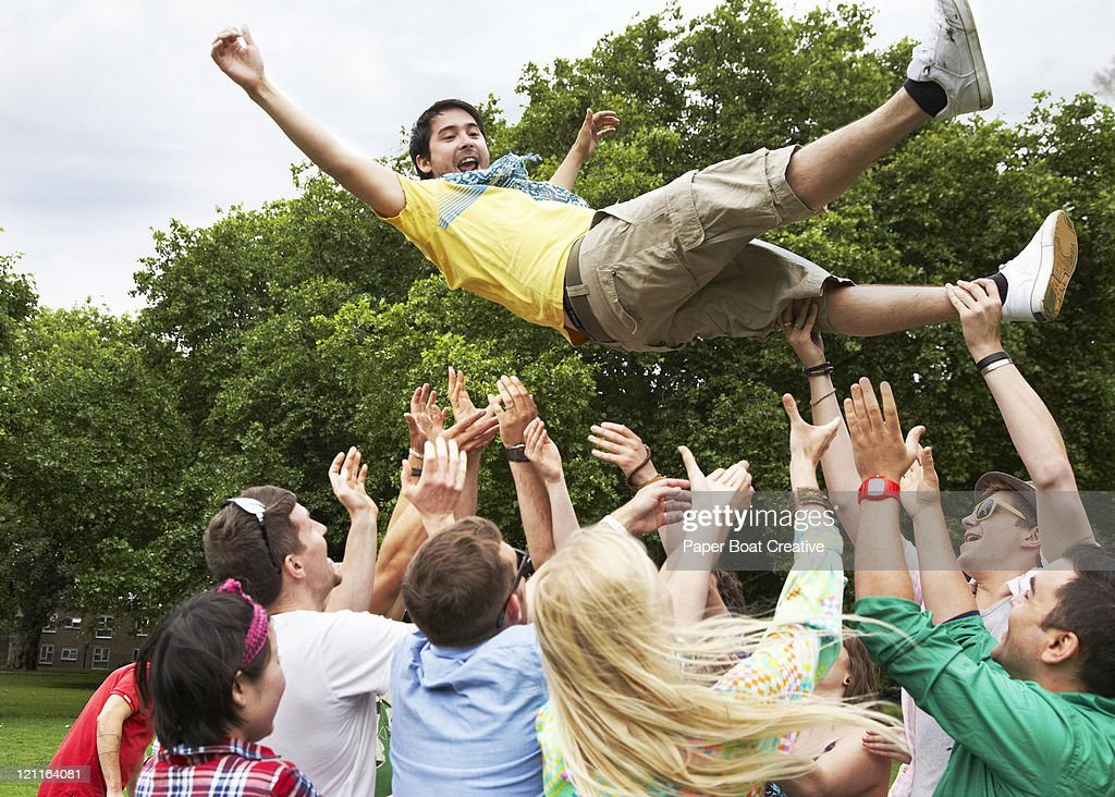 group of friends throwing one man in the air : Stock Photo