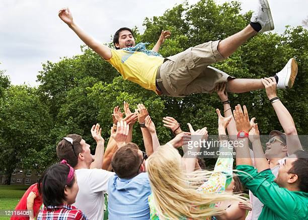 group of friends throwing one man in the air