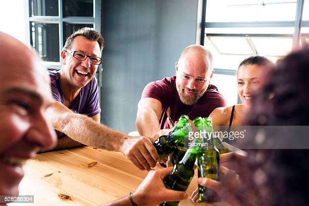 Groupe de amis portant un toast à l'intérieur de la brasserie