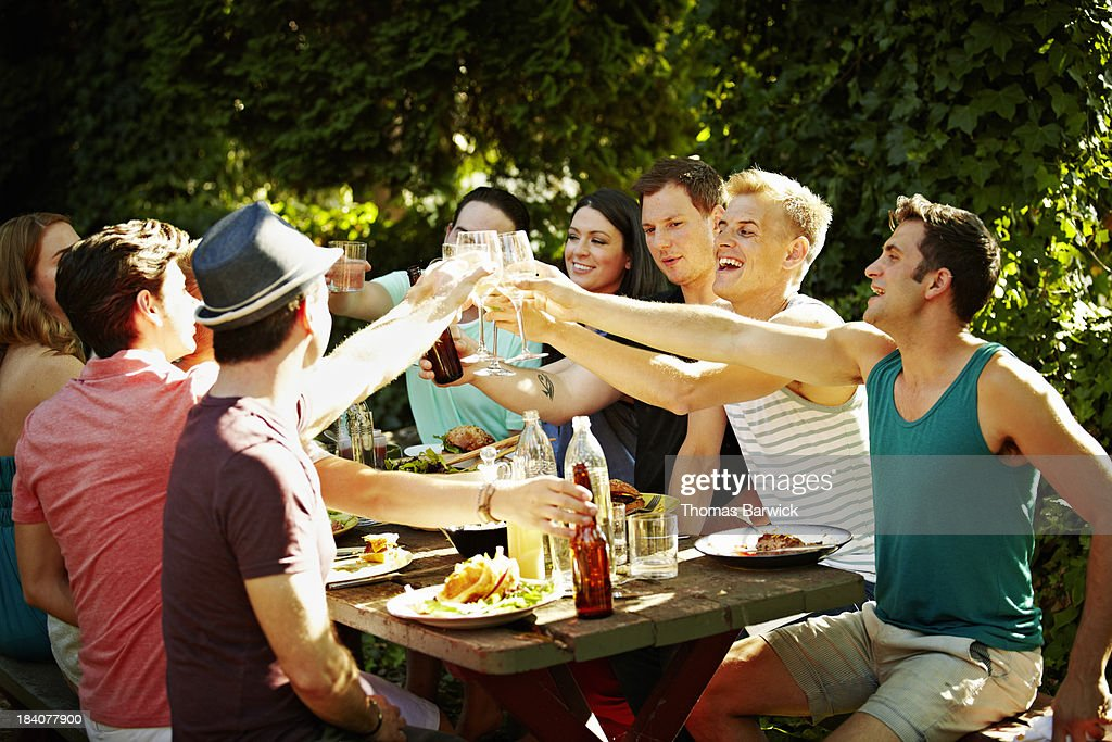 Group of friends toasting at table in backyard : Stock Photo