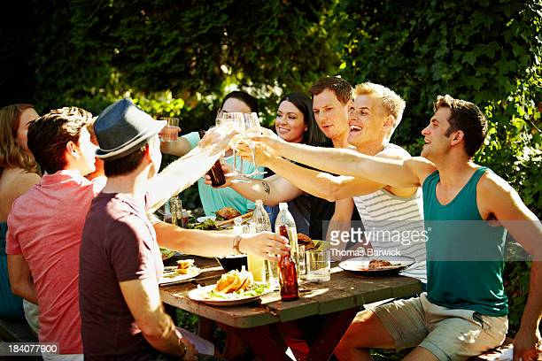 Group of friends toasting at table in backyard