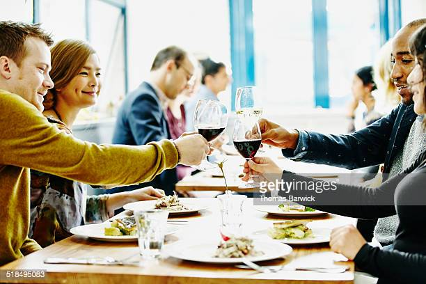 Group of friends toasting at table in restaurant