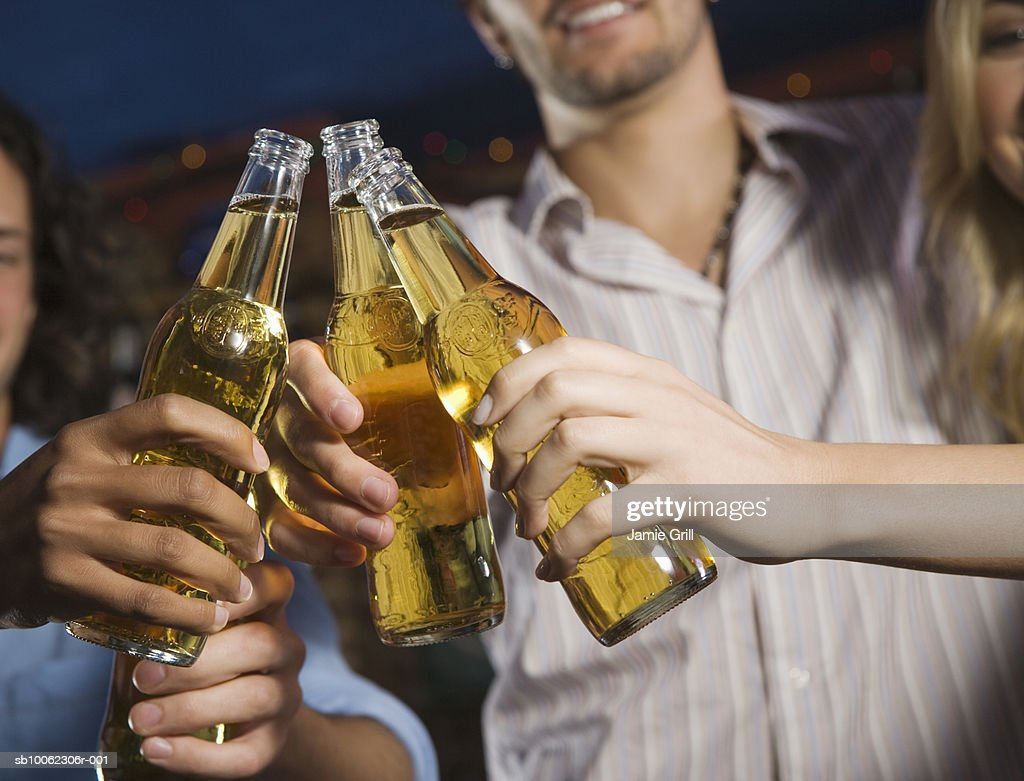 Group of friends toasting beer bottles, close-up : Stock Photo