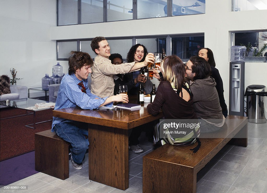 Group of friends toasting drinks in office kitchen : Stock Photo