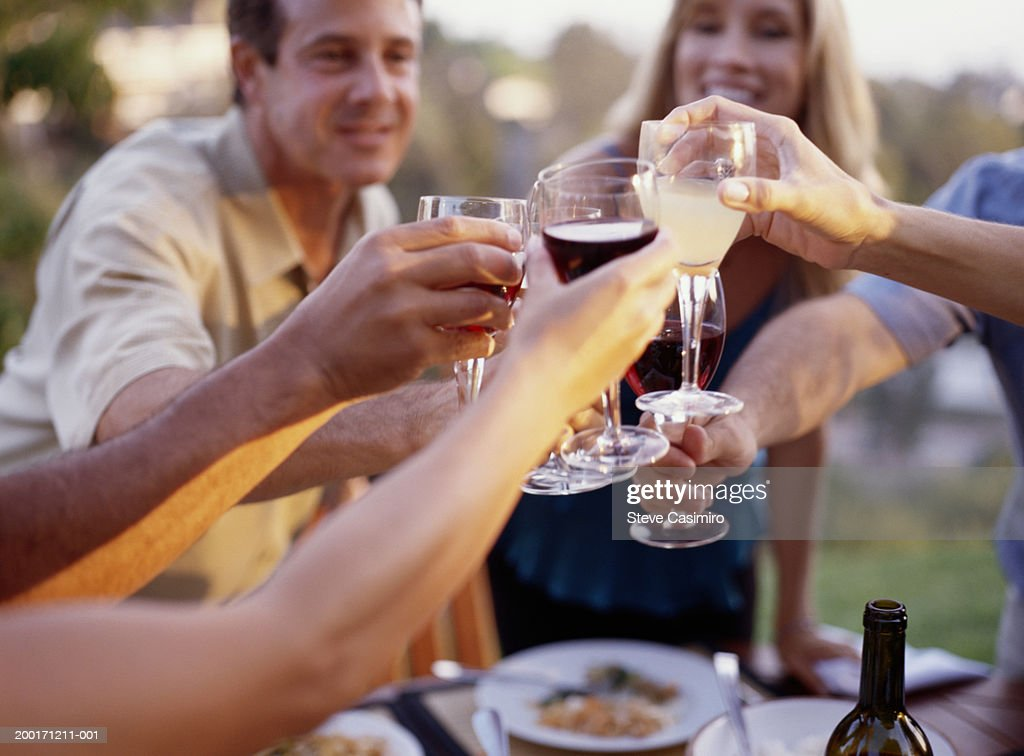 Group of friends toasting drinks, sitting outdoors : Stock Photo