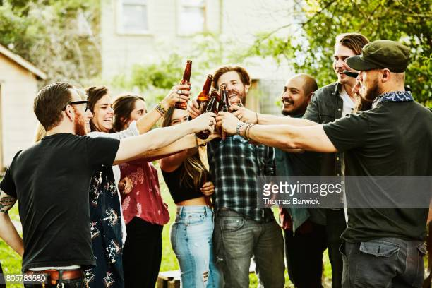 Group of friends toasting during backyard summer barbecue
