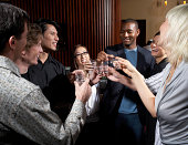 Group of friends toasting in bar, laughing