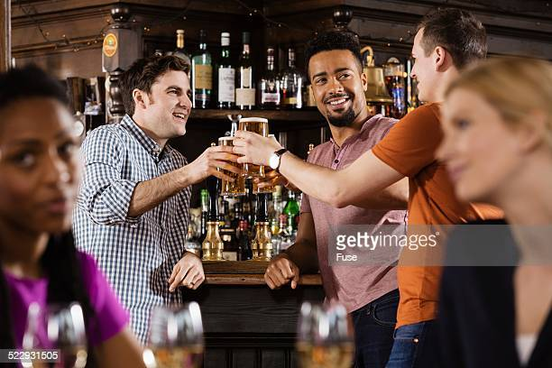 Group of friends toasting in pub