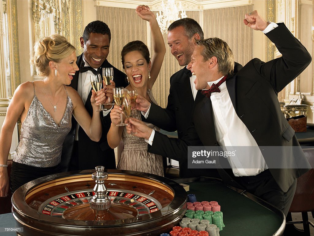 Group of friends toasting wine in casino, laughing : Stock Photo