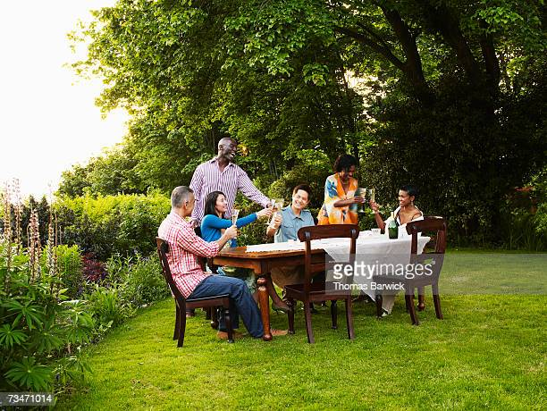 Group of friends toasting with champagne at outdoor dining table, laughing