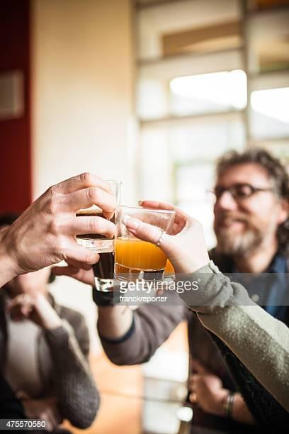 Gruppo di amici brindando con bevande a casa