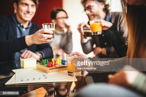 group of friends toasting with drinks at home