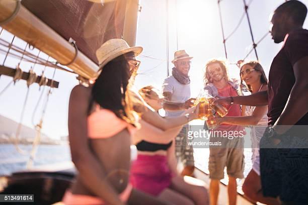 Eine Gruppe von Freunden anstoßen mit Getränken auf einer Jacht