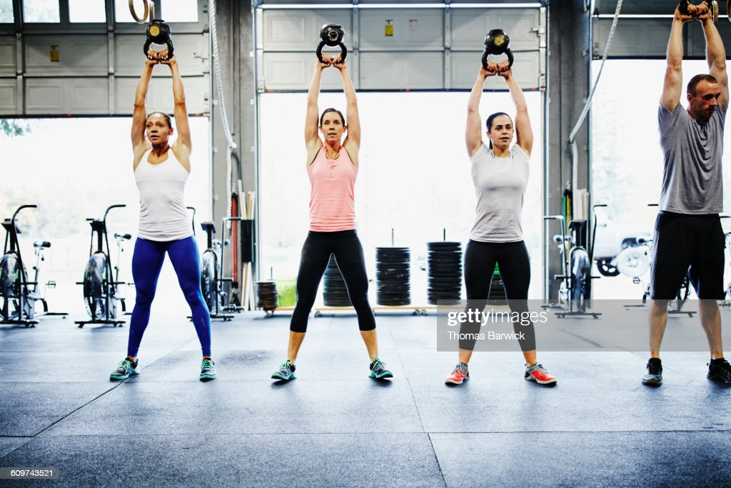 Group of friends training with kettlebells in gym : Stock Photo