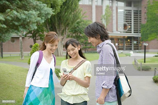 Group of friends using mobile phone on campus
